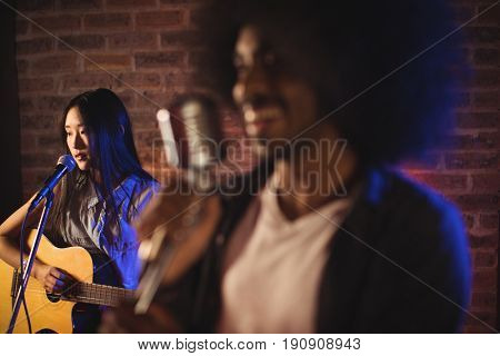 Close up of male singer with female guitarist in nightclub