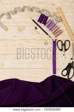 Sewing accessories on a light wooden background of purple and lilac colors. Selective focus.