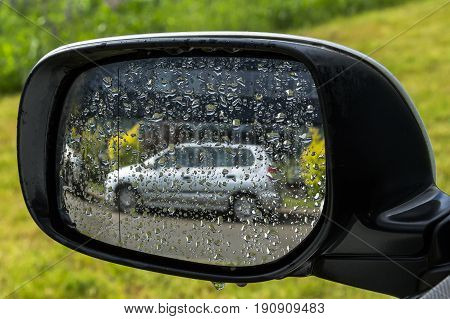Gray car reflection in a wet rear view mirror automotive backgound