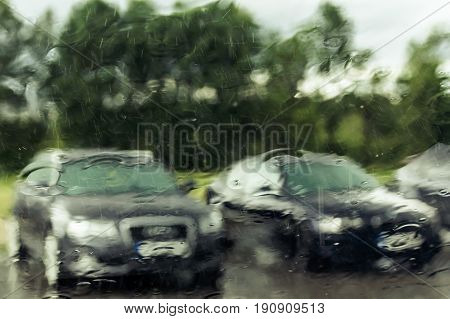 cars through wet windscreen on rainy day abstract background