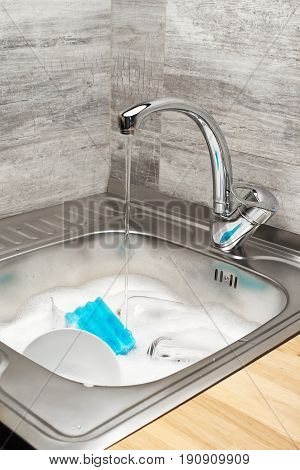 Kitchen Sink With Running Water, Foam, Tableware And Blue Sponge
