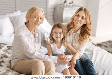 Sense of togetherness. Charming young woman and her sophisticated mother holding hands around the pretty little girl while all of them looking at the camera and smiling pleasantly