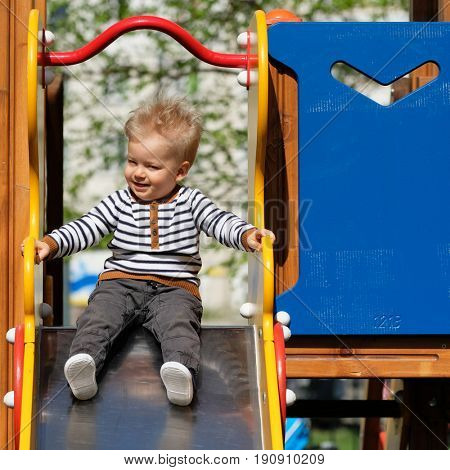 Portrait of toddler child outdoors. One year old baby boy at playground slide