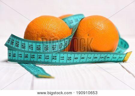 Blue Measuring Tape Wrapped Around Oranges