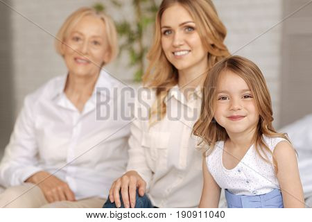 Upbeat mood. The focus being on the pretty little girl sitting on the sofa and looking at the camera while her mother and grandmother being in the background and smiling