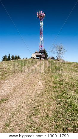 Kamenite hill in Javorniky mountains in Kysuce region in Slovakia with communication tower small wooden view tower big stone mountain meadow with pathway and clear sky