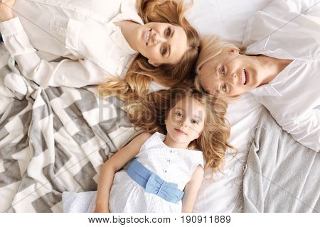 Family harmony. The top view of three pretty cheerful females of three generations, including little daughter and her mother with grandmother, lying on the bed head to head and smiling