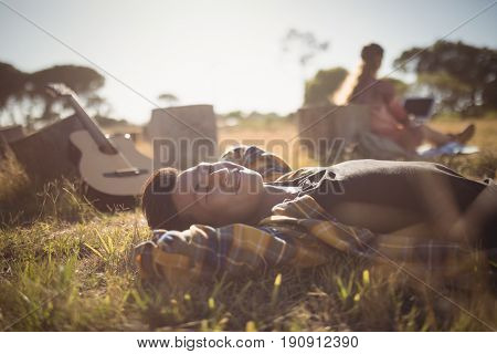 Ypung man with eyes closed resting on grassy field