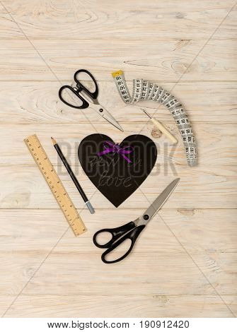 Sewing accessories of purple color and heart with an inscription - sew in love. Selective focus.