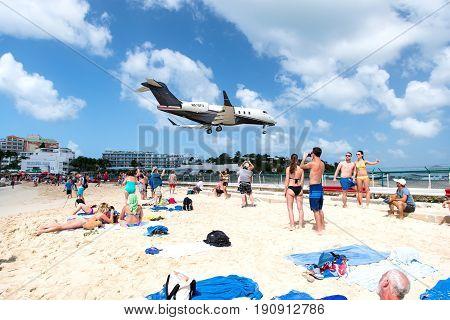 St Maarten Netherlands - February 13 2016: beach observe low flying airplanes landing near Maho Beach on island of St Maarten in the Caribbean