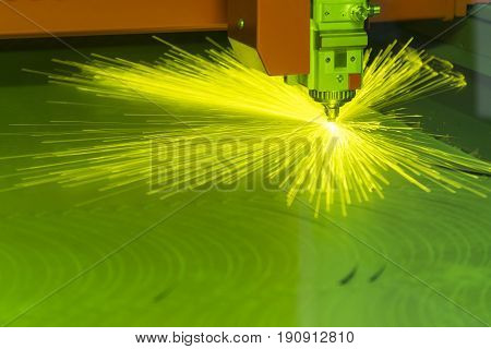 The fiber laser cutting machine cutting the sheet metal with the sparking light.