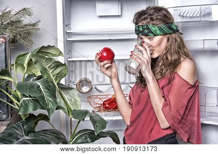 pretty sexy woman hippie with cute face in green handkerchief or bandana on curly hair near fridge plant drink from glass and holds red apple
