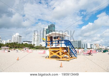 Man Lifeguard Patrolling Beach On Wooden Tower