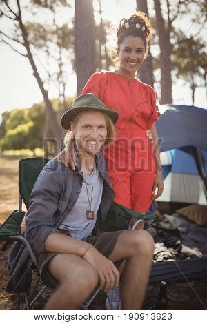 Portrait of smling couple by tent at forest