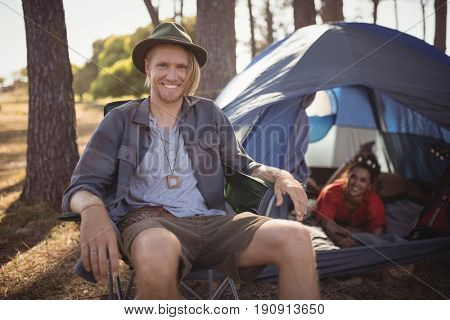 Portrait of smling man sitting on chair by tent at forest