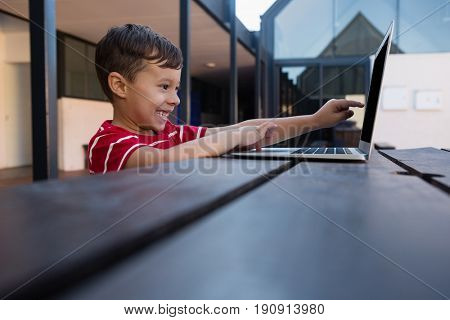 Side view of cheerful boy using digital laptop while sitting at table in school