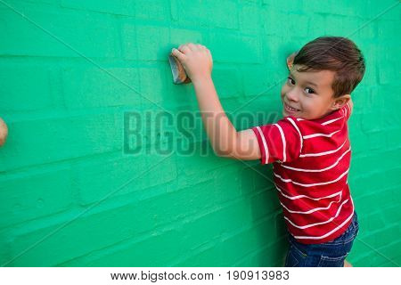 Portrait of smiling boy climbing wall at playground in school