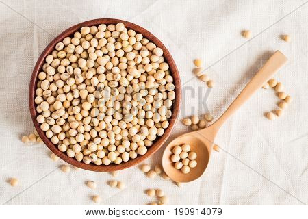 Soybeans in a wooden cup on a table cloth Background,top view