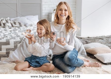 Amusing experiments. Overjoyed little girl holding a box of liquid powder and putting her finger into it while her mother smiling at the camera and holding another powder box and a brush