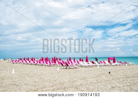 Miami South beach. sandy beach with sunbeds chairs and folded pink umbrellas on blue sea or ocean coast on sunny cloudy sky. Idyllic summer vacation. Lounge and leisure