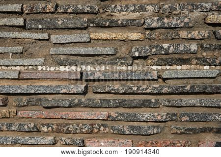 Detail of a wall of thin granite slabs. Slabs include colorful pieces: white gray brown. The slabs are fixed with cement mortar. Texture background