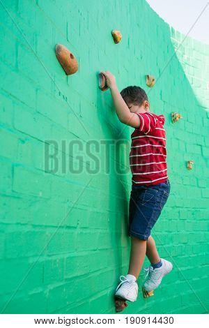 Cute boy climbing wall at playground in school