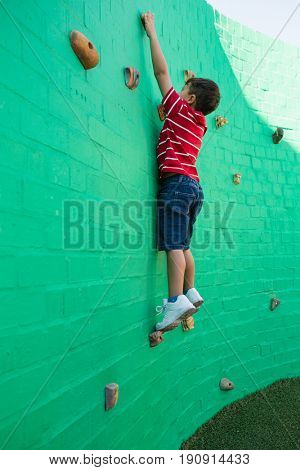 Side view of boy climbing wall at playground in school