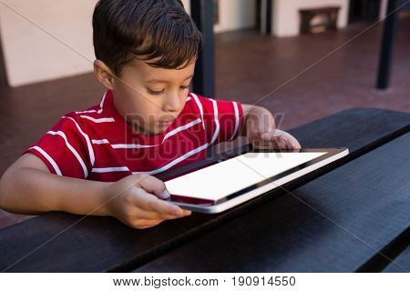 Close up of boy using digital tablet while sitting at table in school