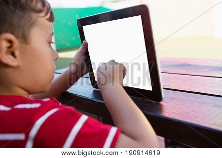 Close up of boy touching digital tablet while sitting at table in school