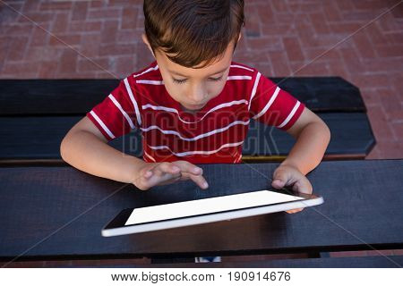 High angle view of boy touching digital tablet while sitting at table in school