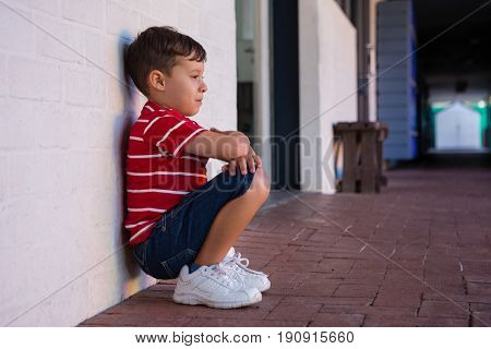 Side view of boy crouching by wall in school building