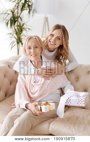 Presents for the dearest. Elegant senior lady sitting on the sofa and holding gift boxes while her beautiful young daughter standing behind the sofa and embracing the mother from