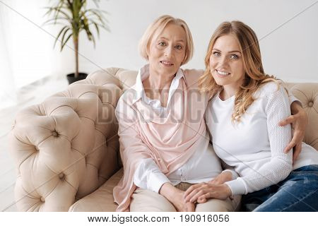 Cuddles on couch. Attractive fair-haired young woman and her sophisticated mother sitting on the couch and cuddling, being seemingly happy to be together