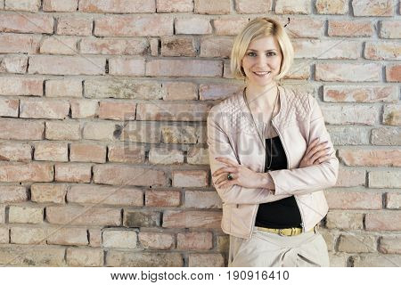 Happy blonde woman standing arms crossed leaning against brick wall.