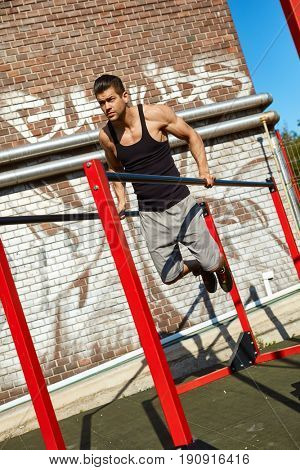 Athletic man doing pushups on parallel bars outdoor.