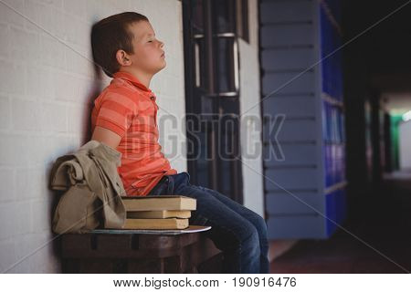 Sad boy with eyes closed sitting on bench by wall in corridor at school