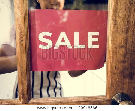 People Put Up Sale Sign on Wooden Door