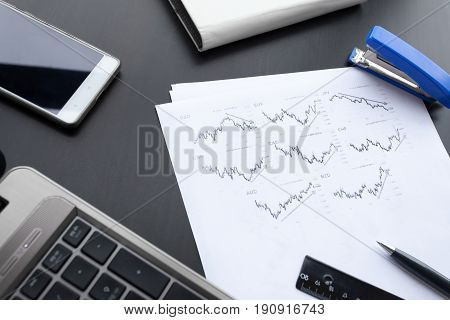 graph paper, laptop, phone and a pen on the office table