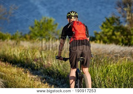 Rear view of the cyclist riding with mountain bike on the trail above river. Sportsman in the black sportwear, with backpack and in the helmet. Beautiful summer landscape. Concept of the healthy lifestyle.