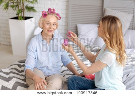 Pleased to help. Young fair-haired woman holding hair rollers in both hands, being about to fix them on the hair of her mother sitting on the bed and smiling at the camera