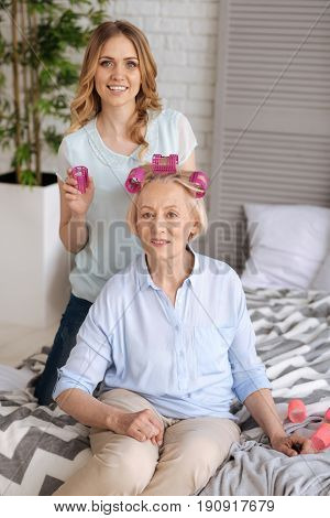 We love primping. Elegant senior woman sitting on the bed and wearing three pink hair rollers while her beautiful young daughter standing on her knees behind the mother and holding a roller in a hand