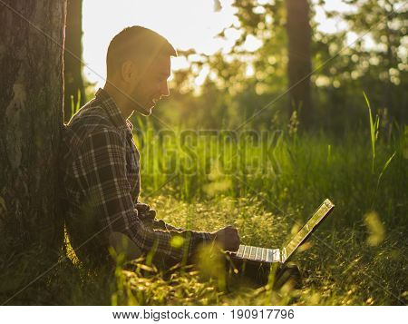 Smiling young man with laptop outdoor in forest