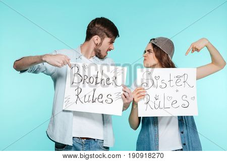 Young handsome brother and pretty sister holding funny nameplates over blue background. Looking aside.