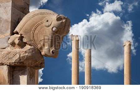 Bull figure used as decorative capital statuary of a column in Persepolis of Shiraz against blue sky with white fluffy clouds.