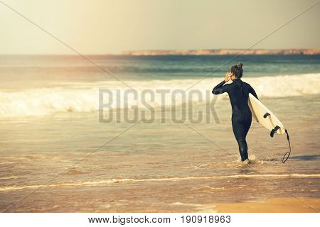 young surfer girl wearing wetsuit going into the ocean to surf at sunset