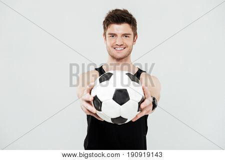 Picture of cheerful young sportsman with foot ball standing isolated over white background. Looking at camera.
