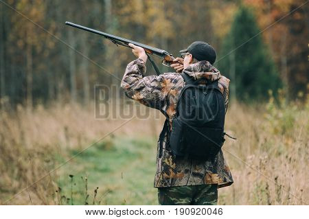 Hunter with hunting rifle in autumn forest