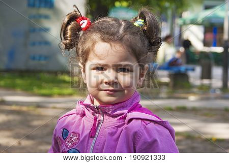 A little girl with pigtails looks at the camera.