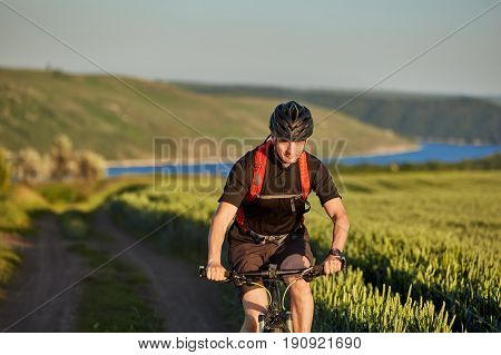 Attractive cyclist riding mountain bicyclist in the summer green field. Young sportsman dressed in the black sportwear, with helmet and backpack. Horizontal photo. Beautiful landscape. Concept of the active and healthy lifestyle.