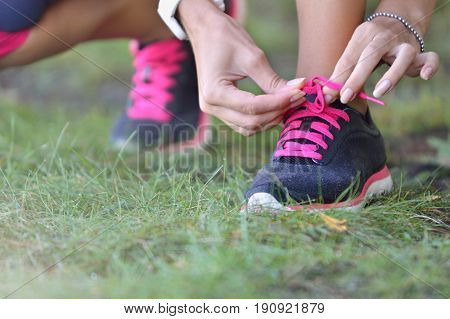 Woman ties up shoelaces on sneakers. Close up view. Healthy lifestyle concept.